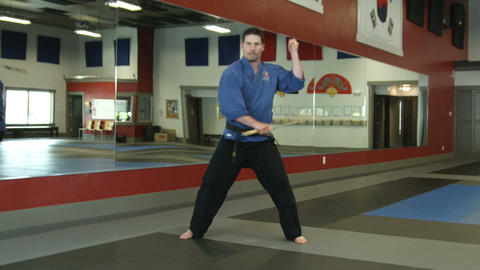 Man in a karate studio practicing nunchuch weapon moves Footage