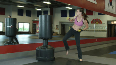 Full body shot of a woman in a gym doing punching and kick combos Footage