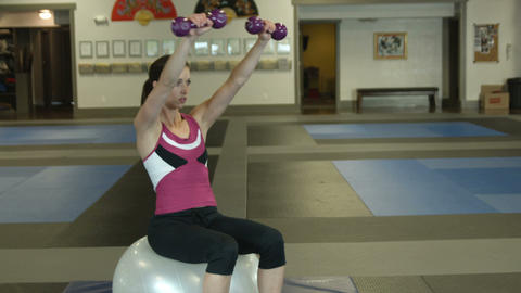 Woman doing arm workouts sitting on workout ball Live Action