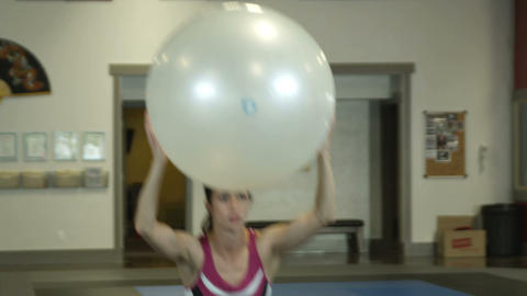 Woman exercising with yoga ball over her head Footage