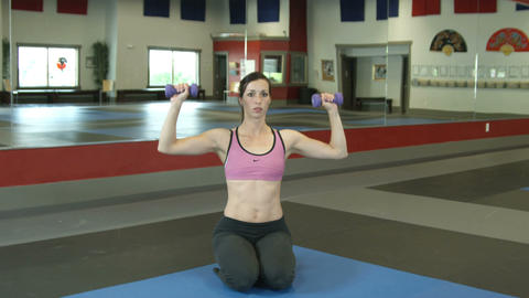 Shot of a woman kneeling on a gym floor lifting weights Footage