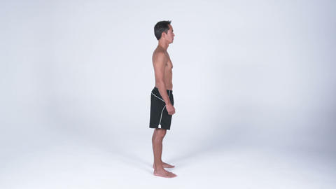 Right side view of a white man in gym shorts standing against a white background Footage