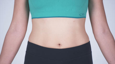 Front view panning shot down of a happy woman in sports bra and gym shorts Footage