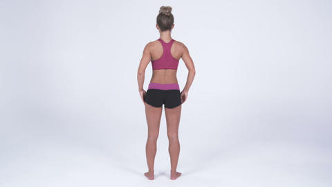 Back view of a young woman in yoga attire places hands on hips Footage