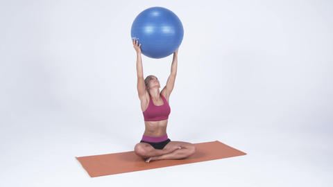 Young woman sitting on a yoga mat lifts a yoga ball above her head Footage