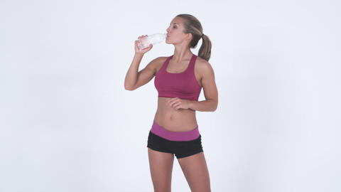 3/4 body shot of a woman in gym attire opening and drinking from a bottle of wat Footage