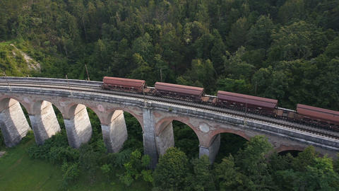 Aerial - View of a freight train crossing the stone railroad bridge Footage