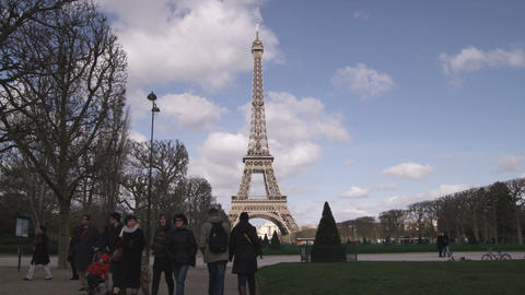 Eiffel Tower and silhouetted people and trees Live Action