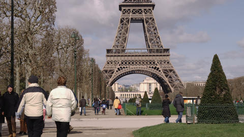 People walking around the base of the Eiffel Tower Live Action