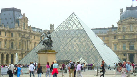 People passing by the glass pyramid of the Louvre Museum Live Action