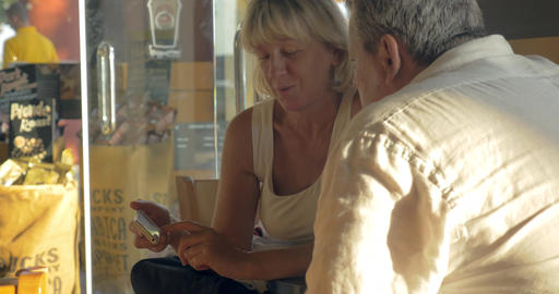 Senior couple with smart phone in cafe Footage
