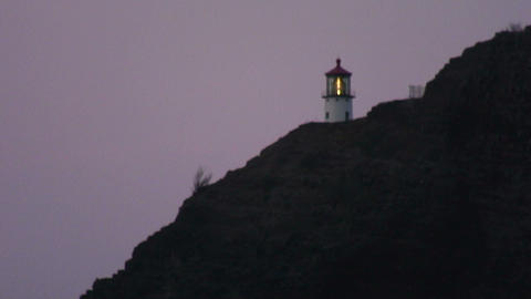 Ocean shoreline at sunset with a lighthouse up on a cliff Live Action