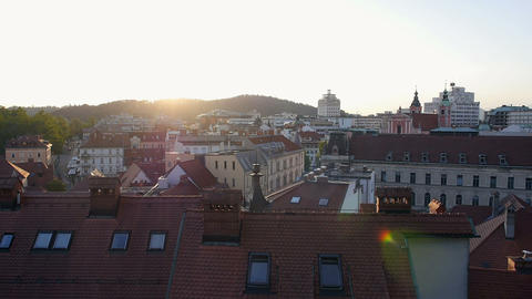 Aerial - Flight over the rooftops above the city at sunset Footage