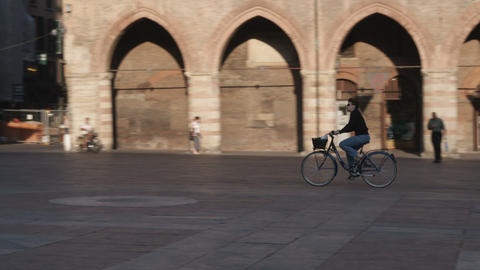 Man riding a bicycle in a plaza in Bologna Italy Live Action