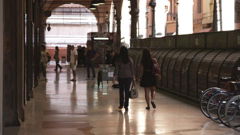 Two women walking down a covered walkway in Italy Footage
