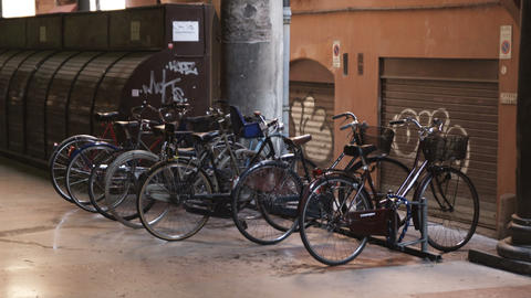 Old bikes parked at a rack in a mall in Bologna Italy Footage