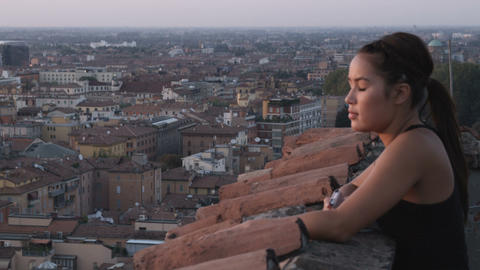 Woman jogger listening to music as she overlooks an Italian cityscape Footage