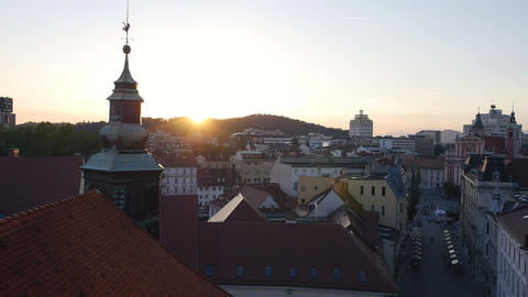 Aerial - Over the church rooftop above the city at sunset Footage