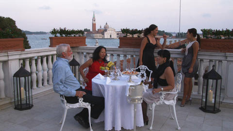 People having dinner on a hotel rooftop balcony overlooking Saint Mark's Canal Footage