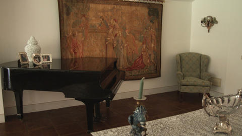 Tilting up shot in a Italian room with a dining table and a baby grand piano Footage