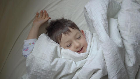 Top view of cute little boy stretching in bed at home Footage