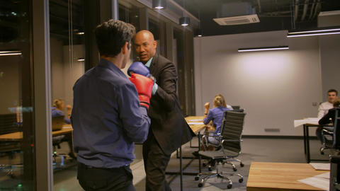 Two Competitive businessmen fighting with boxing gloves in corporate office ビデオ