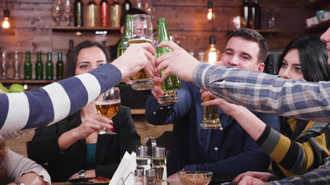 Happy friends clinking their glasses with beer Footage