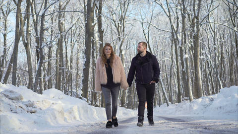 Couple walking in winter park happy and joyful. Beautiful Couple walking in the Footage
