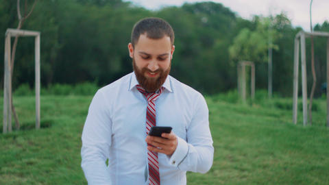 Attractive businessman looking on the mobile phone, feeling happy, seeing good Footage
