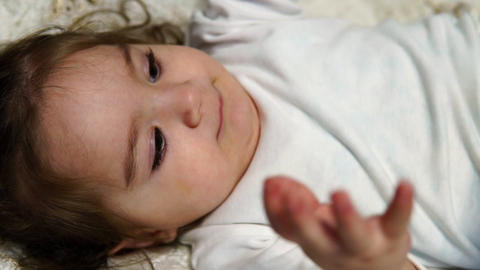 Little girl lying on the bed horizontally, close-up Footage