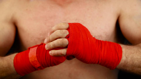 Close up man boxer tightens wrists with red wrap ビデオ