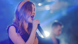 Girl with a microphone sings, indoors, against the backdrop of bokeh. The girl Footage