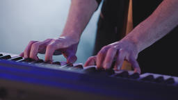 Close up man hands playing electric piano under colorful stage lighting Live Action