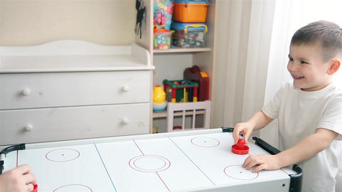 Mom and son play with passion in air hockey ビデオ