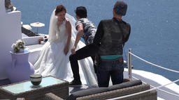 Greece Aegean Sea Cyclades Santorini Oia Bride with photographer team on terrace ビデオ