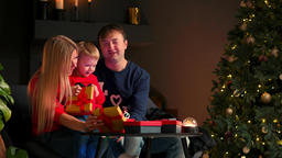 Portrait of happy family opening a Christmas present gift box in the evening Footage