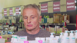 Mature man shopping at the drugstore, examining products on a shelf Live Action