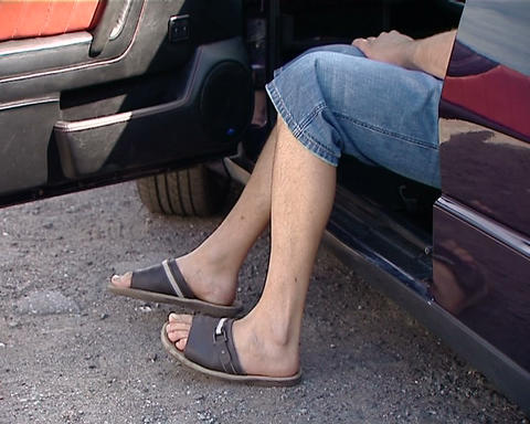 Bare legs sticking out of the car Stock Video Footage