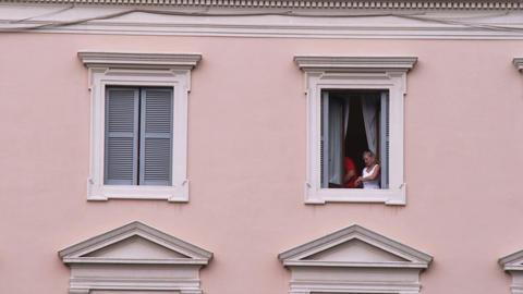 Couple looking out of a window in Rome Italy Footage