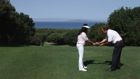 Woman recieving golf instruciton at a golf course overlooking the sea Footage