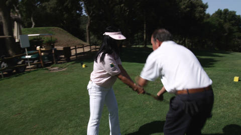 Golf trainer showing woman propper form Footage