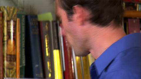 Man reading a book with bookshelves in the background Footage