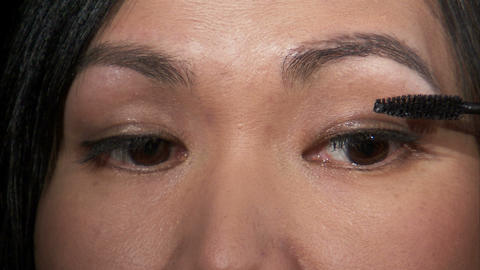 Close shot of a woman putting on mascara Live Action