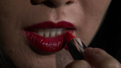 Close shot of a woman putting on lipstick Stock Video Footage