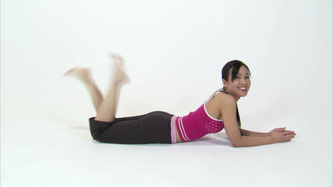 Woman laying on her stomach, kicking her feet, and smiling on a white background Footage
