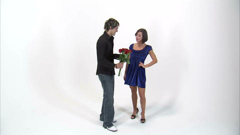Woman taking a bouquet of roses from a man and walking away Footage