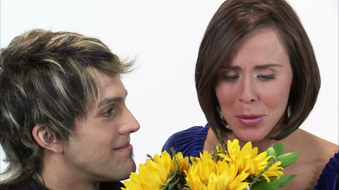 Close-up of a man giving a woman sunflowers then they kiss Footage