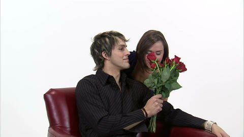 Man gives a woman roses then she kisses him on the cheek Footage