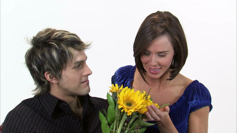 Man gives a woman sunflowers then she kisses him and thanks him Footage
