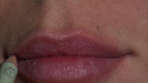 Extreme close up of a woman's lips as lip liner is applied Footage